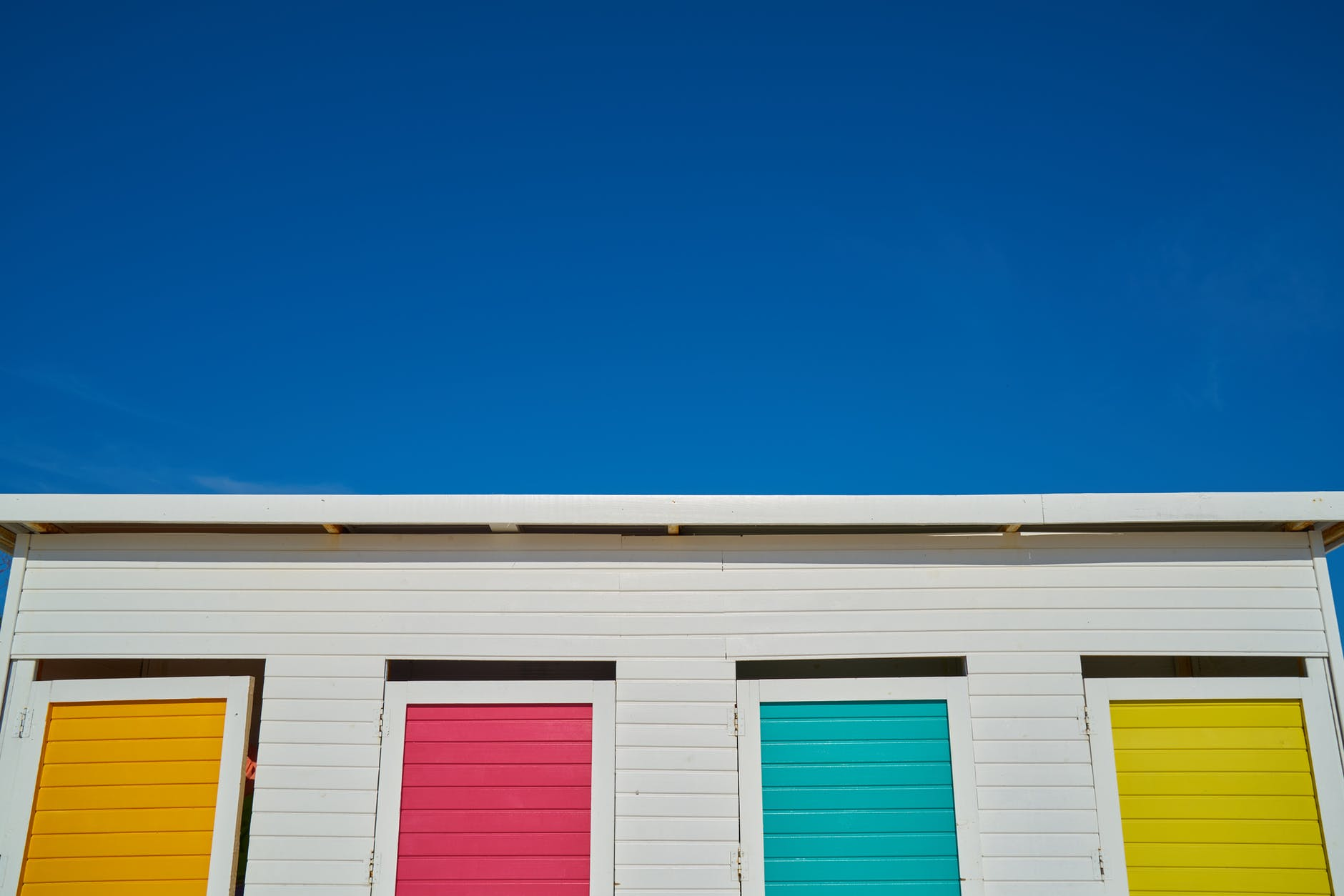 white wooden house with yellow pink green and orange painted windows